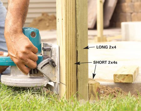 <b>Photo 4: Trim the short 2x4s</b></br> Mark the short side posts a few inches above grade and cut them off with a circular saw. Take care not to cut the long center post.
