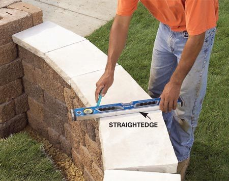 <b>Photo 6: Mark the capstones</b></br> Starting at one end, fit the capstones by butting them together. Lay a straightedge across the joint and mark cutting lines on both stones.