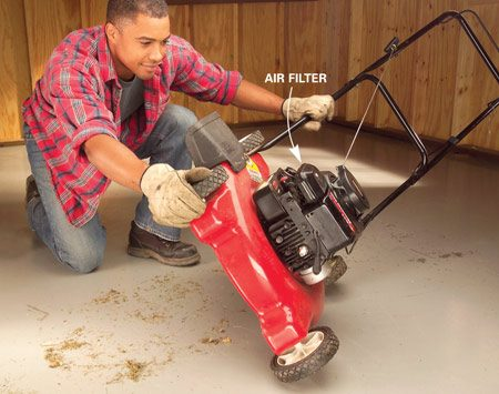<b>Photo 2: Tip mower on its side</b><br/>Turn the mower onto its side with the air filter and carburetor side up. This keeps oil and gas from dripping into the air filter.