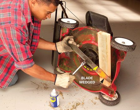<b>Photo 3: Remove the blade</b><br/>Wedge a short 2x4 between the blade and the deck to clamp the blade. Loosen the bolt (or nut) with a long-handled wrench. Turn counterclockwise. Remove the bolt and blade.