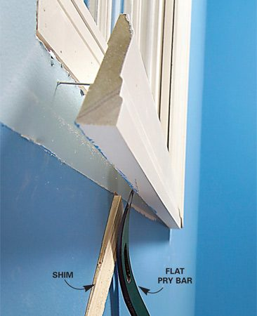 <b>Photo 2: Gently pry trim off evenly</b></br> Pry away the trim gently with a flat pry bar. Protect walls with a shim or a scrap of wood as you gradually work the trim away from the wall.