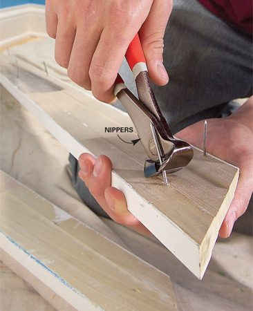 <b>Photo 3: Pull nails out through back of trim</b></br> Pull nails out through the back side of trim with nippers or pliers. Also write the location of each piece of trim on the back side.