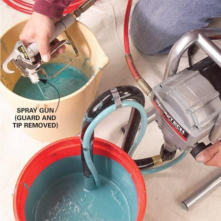 <b>Photo 3: Fill the hose</b><br/><p>Hold the gun  (guard   and spray tip   removed) over  the waste   bucket and pull  the trigger.   Switch the valve  to   the &ldquo;spray&rdquo;  setting. Let   go of the  trigger when   paint is flowing  in a   steady stream  from the   gun. Lock the  trigger and   follow the  &ldquo;Pressure Relief Steps.&rdquo; </p>