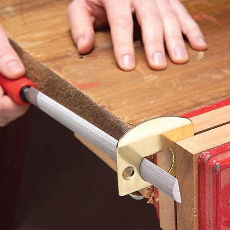 <b>Photo 2: Filing the strike plate</b></br> Remove the strike plate, place it in a vise and enlarge the hole with a file. You may also have to enlarge the hole in the doorjamb.