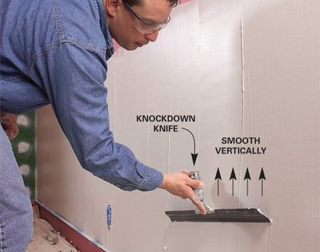 <b>Photo 1: Smooth vertically</b></br> Fill rough and damaged areas with compound and then stroke vertically to smooth the mud with a knockdown knife.
