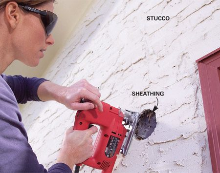 <b>Photo 1: Cut junction box holes</b></br> Cut holes for junction boxes. On stucco, drill a series of holes around the perimeter, break out the stucco with a chisel and then cut the sheathing with a jigsaw.