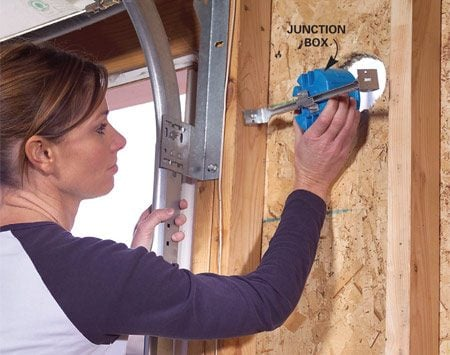 <b>Photo 2: Fasten the junction boxes in place</b></br> Install junction boxes so they're flush with the exterior surface of the wall. Have a helper outside position the box while you fasten it.