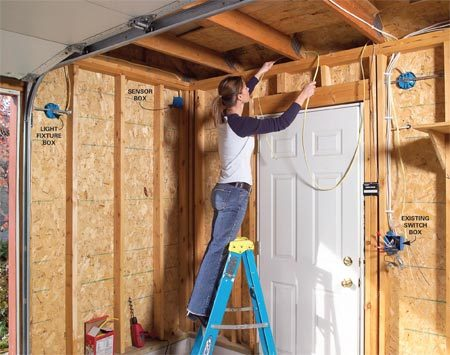 <b>Photo 3: Run cable to junction boxes</b></br> Drill 5/8-in. holes in the center of the wall framing to create a path for cable. Then run the cable between the junction boxes. Fasten the cable to framing with plastic cable staples.