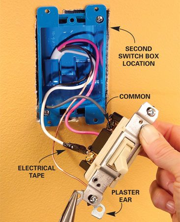 <b>Photo 6: Attach the second switch</b></br> Clamp the second electrical box to the wall and wire a three-way switch, following Figure B. Snap off the plaster ears and install the switch.