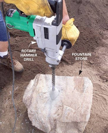 Rent a rotary hammer drill and a long masonry bit to<br/> drill a hole in the stone.