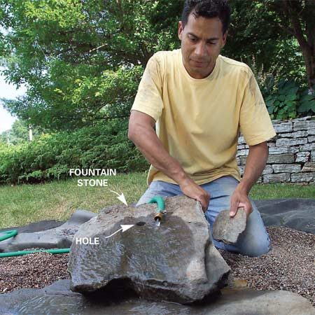 <b>Photo 10: Adjust the fountain builders and test the water's path</b></br> Place and roughly adjust the fountain boulders using a garden hose placed near the fountain hole to simulate the water's path. Then flip over the boulder to access the underside of the hole.