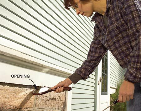 <b>Photo 1: Check the foundation/siding joint</b><br/>Inspect the underside of your siding using a mirror. If you find a gap, mark the location with masking tape so you can seal it later.