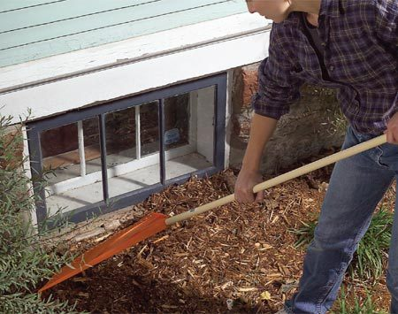 <b>Photo 1: Protect wood from moisture</b><br/>Rake moisture-wicking soil and mulch away from the window frames and low wood. Turn your mulch periodically to help keep dampness down, and keep bushes trimmed back as well.