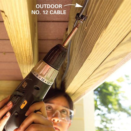<b>Photo 2: Run cable</b></br> Fasten the supply cable out of sight under the deck using cable clamps. Drill holes and run it through framing as needed.