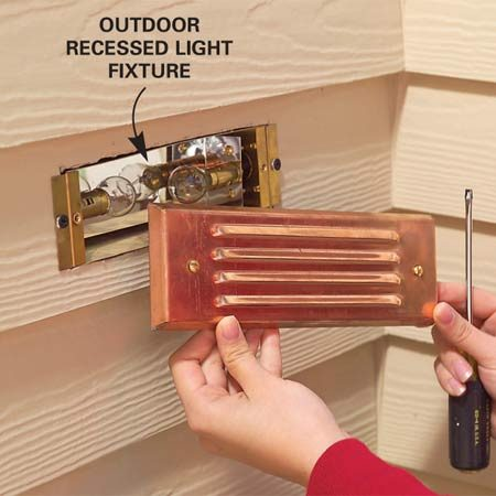 <b>Photo 4: Install fixtures</b></br> Push the wires into the recess behind the fixture, screw the fixture to the siding and install the lamps and cover.