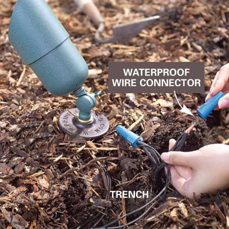 <b>Photo 8: Bury wires and connectors</b></br> Aim the ground-level spots, and join the wires with waterproof connectors. Then bury the cable and connectors 6 in. deep.