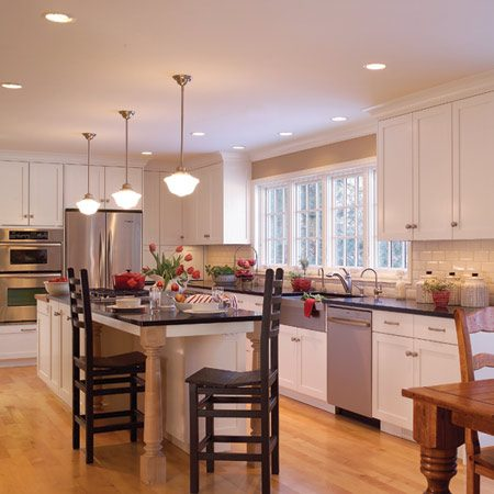 """<b>The completed kitchen: Loads of storage space and a lot of light</b></br> Cabinets designed for optimum storage can't do their job without optimum light. Spectacular windows bring in loads of daylight, while three rows of unobtrusive recessed fixtures work the late shift. The recessed lights directly over the sink contain spotlights and provide focused, shadow-free illumination for food prep and cleanup. The other two rows are centered over the """"traffic patterns"""" and contain floodlights for general illumination of the floor and upper cabinets. Pendant lights over the island hang low enough to illuminate the countertop and cooktop, but high enough to avoid shining directly into anyone's eyes."""