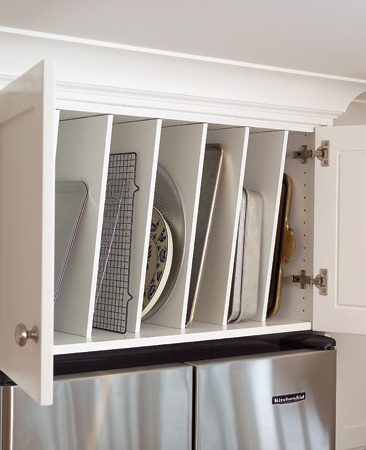 <b>Over the fridge storage</b></br> The above-refrigerator cabinet contains vertical partitions for storing trays, flat pans and cutting boards.
