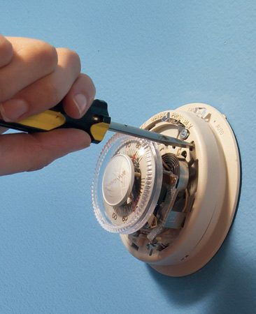 <b>Photo 1: Remove the cover</b></br> Pull off the cover ring and remove the screws that fasten the thermostat to the wall plate.