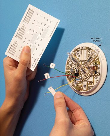 <b>Photo 2: Label the wires</b></br> Label the wires as you disconnect them from the screw terminals. Then remove the mounting screws that fasten the wall plate.