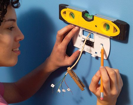 <b>Photo 3: Attach the mounting plate</b></br> Mark the new screw locations, drive in wall anchors and screw the mounting plate to the wall. Connect the wires.