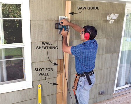 <b>Photo 3: Cut through the siding</b></br> Make a mark 1-5/8 in. out from the deck on both sides. Then make another mark 5-1/8 in. inside the first mark. Draw plumb lines up from these marks and cut a 5-1/8-in. slot through the siding but not the sheathing.