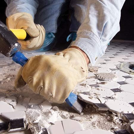 <b>Chisel up tiles</b></br> Work the chisel between the tiles and the concrete, hammering them up with a 2-lb. maul.