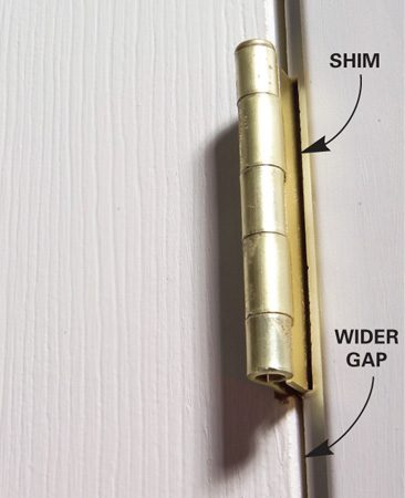 <b>Photo 2: Insert shims</b></br> Follow the same procedure for each hinge. The gap along the hinge side should open about 1/16 in. and narrow the gap on the latch side.