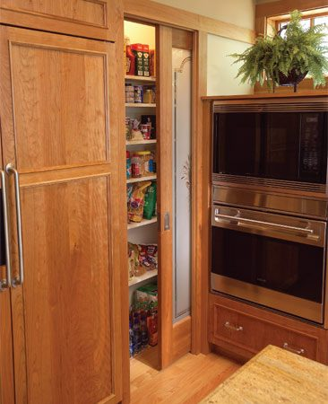 <b>Reach-in pantry</b></br> A glass-front pocket door that slides into the wall cavity instead of taking up precious floor space provides easy access to a pantry occupying a potentially awkward corner area.