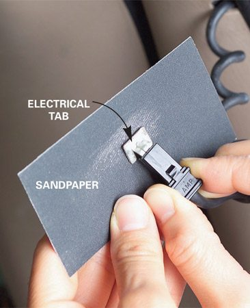 <b>Photo 1: Sand the tab</b></br> Using light pressure, sand the back of the broken tab smooth. Use the sandpaper from the kit.