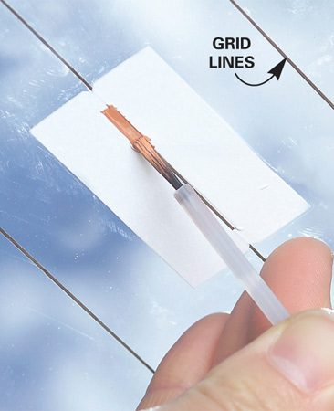 <b>Photo 5: Paint a new line</b></br> Repair a broken grid line by cleaning the area around the break with the alcohol prep. Allow to dry. Peel the wax paper liner off the stencil and apply the sticky side to the glass, aligning the stencil to the existing grid line. Brush on the conductive paint. As with the tab repair, let it dry for 24 hours before using the defogger.