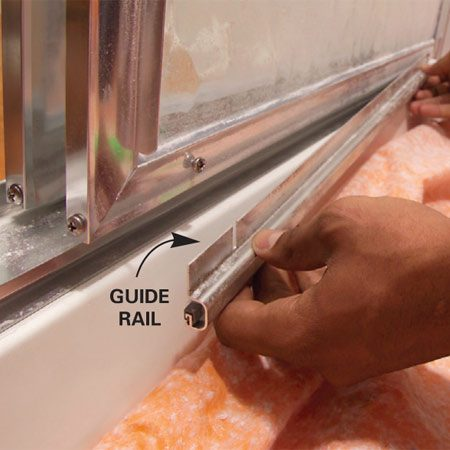 <b>Photo 1: Remove the guide</b></br> Unscrew the guide at the lower edge of the sliding door. Protect the shower or tub from scratches with a drop cloth.