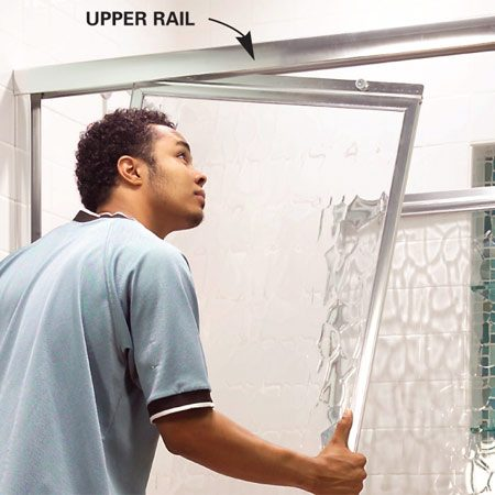 <b>Photo 2:  Remove the doors</b></br> Lift the door out of its track inside the upper rail. Tilt each door in or out to remove it. Wipe both tracks clean.