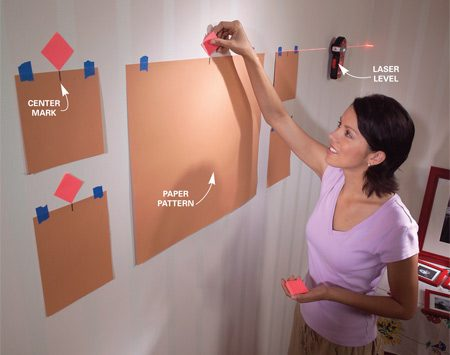 <b>Photo 1: Level and align</b></br> Project a level line and tape exact-size paper patterns on the wall. Mark the top center of each pattern with the corner of a sticky note.