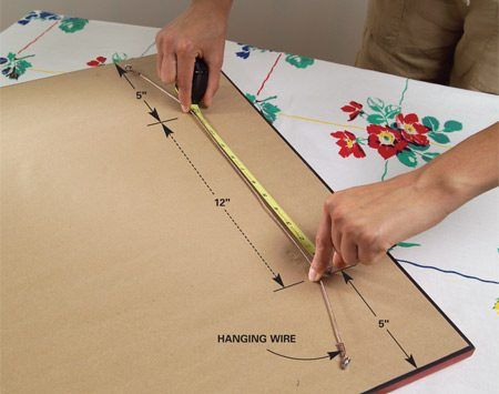 <b>Photo 2: Find hanger locations</b></br> Stretch the hanger wire with two fingers spaced equally distant from the edges of the picture frame. Keep the wire parallel to the top of the frame. Measure the distance between your fingertips.