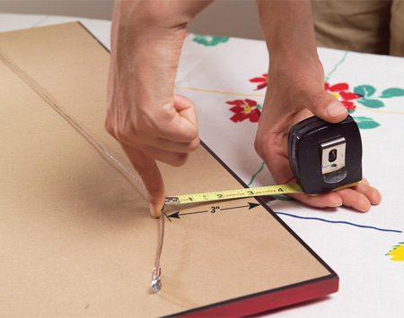 <b>Photo 3: Find distance from top edge</b></br> Leave one finger in place and measure from the wire to the top. Use this dimension and the dimension from Photo 2 to position the picture hangers.