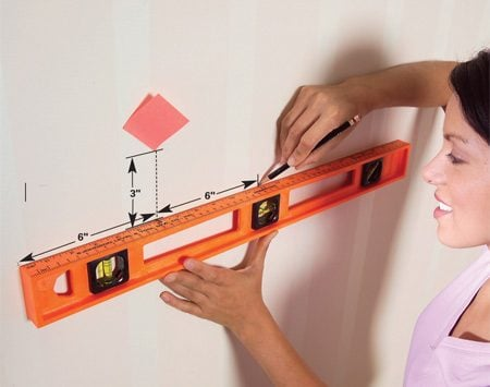 <b>Photo 4: Transfer measurements to wall</b></br> Find the hanger positions by measuring down from the sticky note and to each side from center. Keep the hangers level.