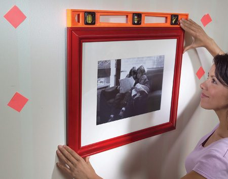 <b>Photo 6: Hang the picture</b></br> Slip the wire over both hooks. Slide the picture sideways across the wires until it's level. Use the same process to hang the remaining pictures.