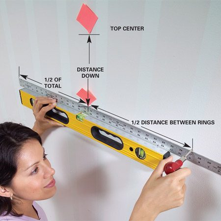 <b>Photo 3: Transfer measurements</b></br> Use a level and a ruler to plumb down the correct distance. Mark the spot with the corner of a sticky note. Then use the level and ruler to find the exact hanger positions.
