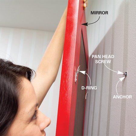 <b>Photo 5: Hang the mirror</b></br> Screw a pan head screw into the anchor. Leave the screw sticking out about 1/4 in. Hook the D-rings onto the protruding screws.