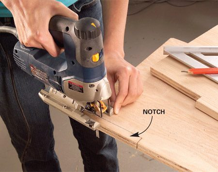 <b>Photo 2: Cut notches in the dividers</b></br> Use a jigsaw to cut notches for your baseboard so the vertical dividers will fit over it.
