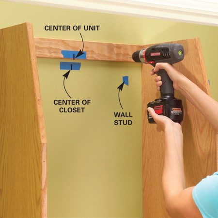 <b>Photo 5: Install the center unit</b></br> Set the center unit in the closet, level it with shims, predrill and tack the hook strips to the wall studs with 6d finish nails.