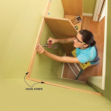 <b>Photo 6: Install the hook strips</b></br> Level the hook strips with the top of the dividers, then predrill and nail them to the studs. Continue the strip around the closet sides.