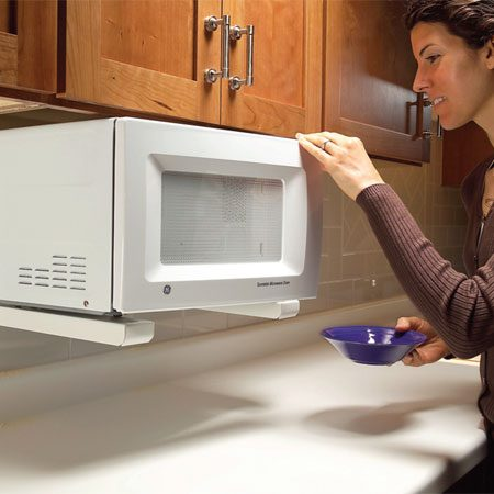 <b>Photo 2: Microwave mounted under the cabinet</b></br> Microwave ovens are the biggest space hogs on most countertops. With a few models, manufacturers offer optional mounting kits that let you mount the microwave under cabinets. To raise your old microwave, consider the sturdy brackets shown here. But first measure its height and the height of the space above the countertop; with a larger microwave, you might find that the space under it will be too small to be useful.