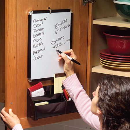 <b>Photo 5: Dry-erase message board</b></br> Don't let shopping lists, phone messages and to-do notes clutter up counter space. Mount a dry-erase board and a plastic bin on the inside of a cabinet door with double-sided foam mounting tape. The bin will protrude into the cabinet, so be sure to position it where it won't collide with shelves or the stuff inside. Get the board, bin and tape at a discount or office supply store.