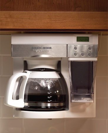 <b>Photo 9: Coffee maker under the cabinets</b></br> For serious coffee drinkers, stowing the coffeemaker inside a cabinet just doesn't make sense; you'll only have to pull it out again in a few hours. Here's a solution: An under-cabinet coffeemaker is always available and doesn't take up valuable counter space.