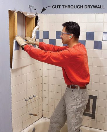 <b>Photo 1: Remove the wall</b></br> Remove the faucet valve handles and escutcheons. Cut through the drywall that surrounds the tile with a utility knife and pull chunks from the wall.