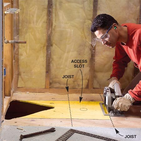 <b>Photo 5: Cut an access slot</b></br> Mark and cut an access slot in the subfloor for roughing in the new P-trap and drain line. Cut over the center of joists where possible.