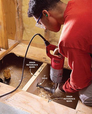 <b>Photo 6: Cut a path for the drain</b></br> Drill 2-in. holes through the floor joists for the new drain line. Reference marks help you find the drain center later.