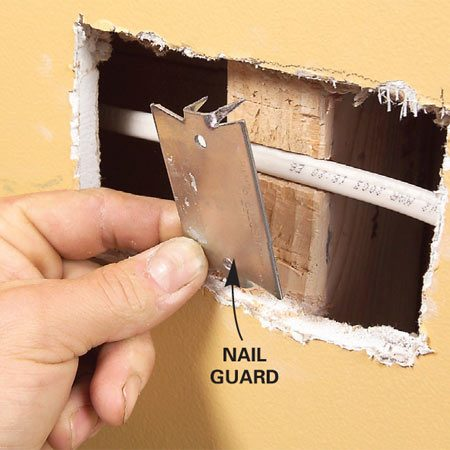 <b>Photo 4: Protect wires from nails</b></br> Press the cable into the notches and cover it with a nail guard for protection.